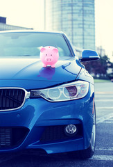 car with piggy bank on hood corporate building background