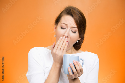 sleepy yawning woman holding cup of coffee on orange background