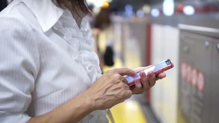 駅のホームでスマートフォンを操作する女性