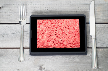 Table setting with fresh raw ground lean beef on a tablet screen