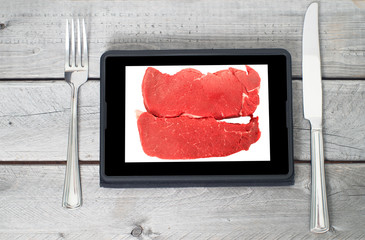 Two raw steaks on a tablet screen with a fork and a knife