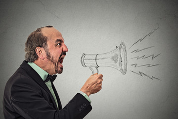 Angry screaming guy holding megaphone on grey background