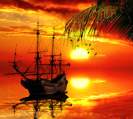old sailboat on a sunset skyline in tropical paradise