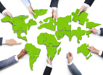 Business People with Jigsaw Forming in World Map