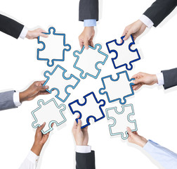 Business People Hands Holding Pieces Of Puzzle