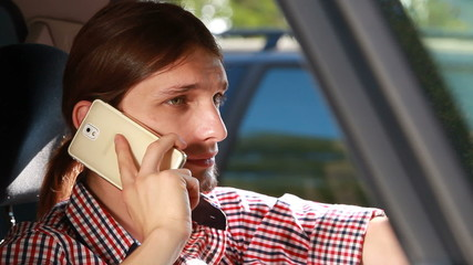 Man sitting in car talking on cell phone