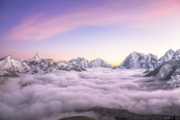 Mountain valley filled with curly clouds at sunrise. Himalayas.