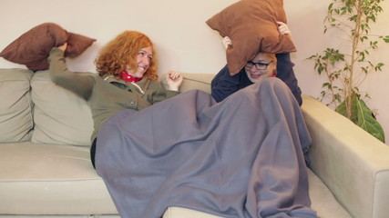 Hilarious happy girlfriends having pillow fight at home.