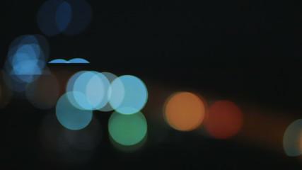 Circular defocused traffic lights moving at night.