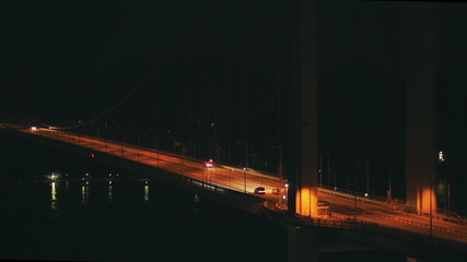 Traffic moves across a massive bridge at night