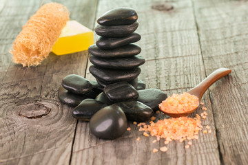 Black stones and bath salt on weathered deck