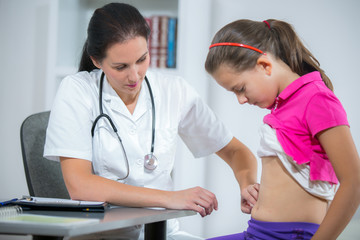 Doctor checking stomach of sick girl