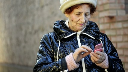 close up of senior woman using mobile phone outdoor