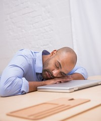 Businessman sleeping by laptop at desk
