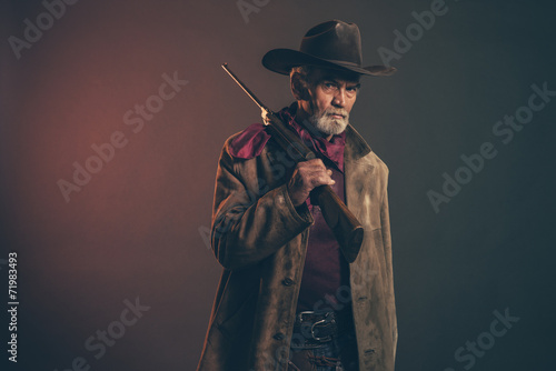 Fototapeta Old rough western cowboy with gray beard and brown hat holding r