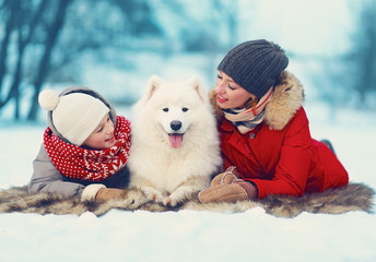 Beautiful happy family, mother and son walking with white dog