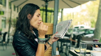 Woman eating lunch and reading gazette in the cafe, steadycam