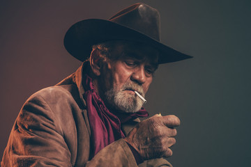 Old rough western cowboy with gray beard and brown hat lighting