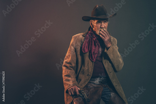 Old rough western cowboy with gray beard and brown hat smoking a - 71983631