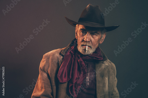 Old rough western cowboy with gray beard and brown hat smoking a - 71983655
