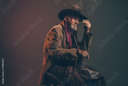 Old rough western cowboy with gray beard and brown hat smoking a - 71983672