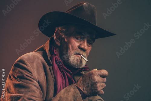 Old rough western cowboy with gray beard and brown hat lighting - 71983689