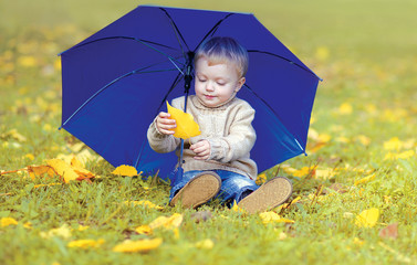 Cute little child with umbrella in autumn park