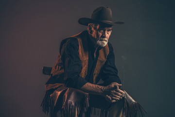 Cigarette smoking old rough western cowboy with gray beard and b