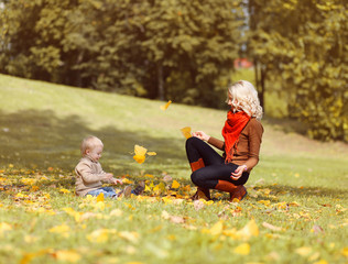 Mother and child playing and having fun in autumn park