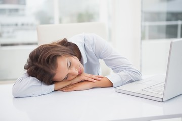 Tired businesswoman sleeping at her desk
