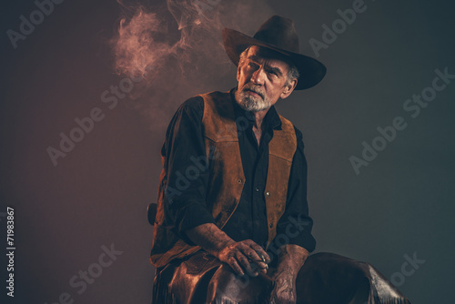 Cigarette smoking old rough western cowboy with gray beard and b - 71983867