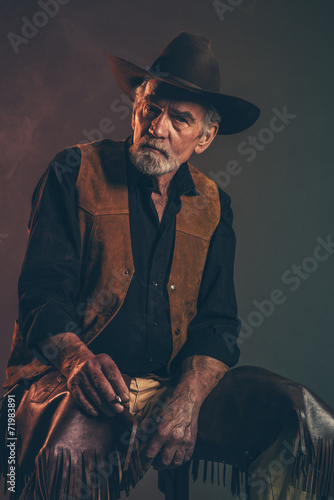 Cigarette smoking old rough western cowboy with gray beard and b - 71983891