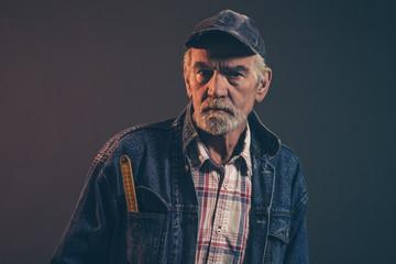 Senior carpenter with gray hair and beard holding yellow measuri