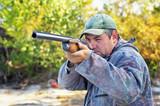 Hunter taking aim at the target. Hunter with a gun.