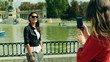 Woman doing photo of her friend in the park, steadycam shot
