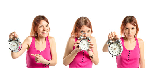 Serious redhead girl holding a clock over white background