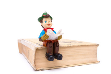 Pinocchio sitting on book isolated on white background