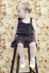 Young girl sitting on stool looking away