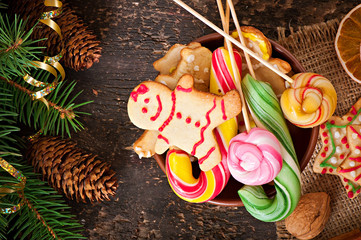 Christmas gingerbread cookies and lollipops on old wooden backgr