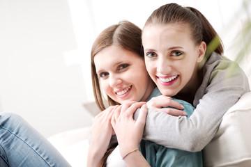 Girlfriends hugging on sofa