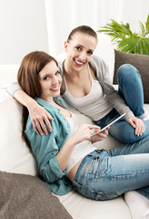 Happy lesbian couple with tablet