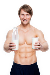 Young handsome muscular man holds milk.