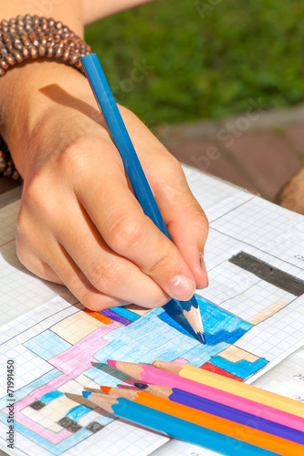 Child hand draws the minecraft picture. Outdoors close-up.