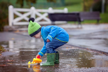 Little boy, jumping in muddy puddles