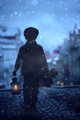 Silhouette of boy, standing on stairs, holding lantern and teddy