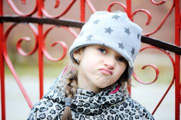 Little angry girl portrait outside
