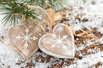 Wooden hearts on snow-covered wooden background.