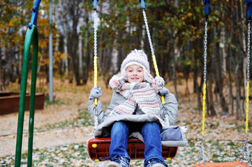 Kid girl  on a swing at beautiful winter day