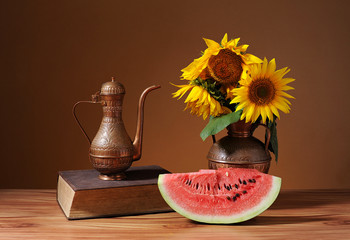 Sunflowers in a vase and fresh watermelon