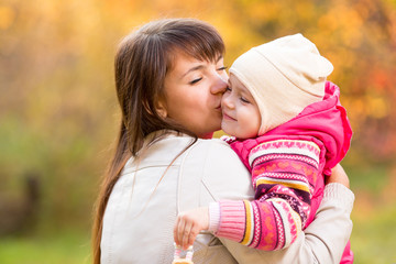 Happy woman and kid in golden autumn background. Mom kissing dau